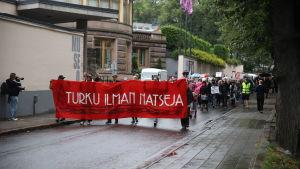 Demonstranter marscherar och bär en banderoll.
