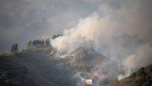 Ett rökmoln svävar ovanför Artenara-området på Gran Canaria då de stora skogsbränderna rasar på ön sommaren 2019.