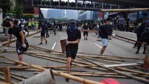 Demonstranter blockerar väg i Hongkong.
