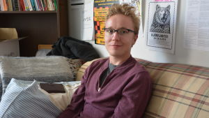 En blond man sitter i en soffa.