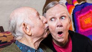 äldre man kysser äldre kvinna på kinden, hon ser förvånad ut