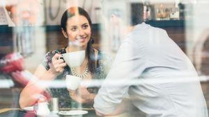 kvinna och man sitter på café, hon ler mot honom