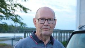 En skallig man med glasögon.