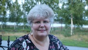 En medelålders kvinna med glasögon och grått hår
