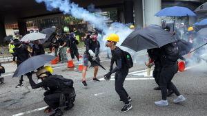 Demonstranter kastar tillbaka tårgasgranater mot polisen i Hongkong