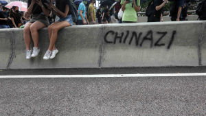 Demonstranter sitter på en betongmur som målats med texten Chinazi.