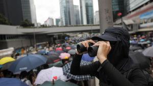 En demonstrant med kikare i Hongkong