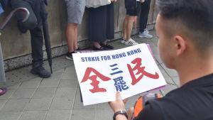 Terry Cheung delade ut affischer åt demonstranterna. I hasten hade det uppstått ett tryckfel i den engelska texten.