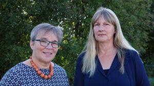 Två kvinnor står framför ett grönt buskage.