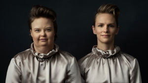 Skådespelarna Karolina Karanen och Sophia Heikkilä står i silverfärgade dräkter och ser rakt in i kameran.