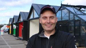 En man med keps på huvudet står framför en rad med små bodar.