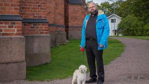 Kaplan Karl af Hällström med sin hund Pyry utanför Lovisa kyrka.