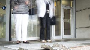 Kaksi vanhempaa naista seisoo oven edessä.