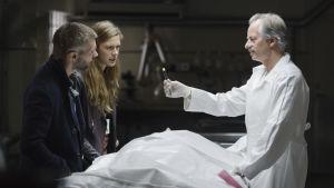 Lars (Nicolai Cleve Broch) och Alfhildr (Krista Kosonen) står i en obuktionssal och stirrar på en del som läkaren håller fram.