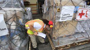 En hjälparbetare koordinerar en frakt med humanitärt bistånd som ska transporteras från Panama City till det orkandrabbade Bahama.