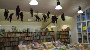 Bokhyllor i bibliotek fyllda med böcker. I taket hänger mjukisdjur. De är alla apor.
