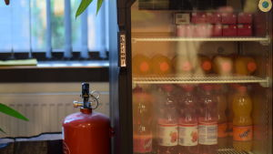 Ett kylskåp med drycker intill en skumsläckare.