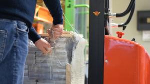 En man bakifrån sm klipper upp plastet på en hög med tidningar.