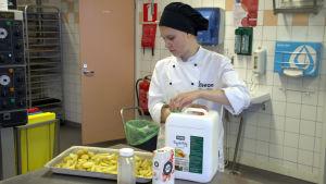 Elev klyftar potatis i övningskök.