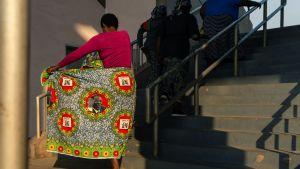 En kvinna på väg till Robert Mugabes begravninsceremoni, i kläder prydda med hans portätt.