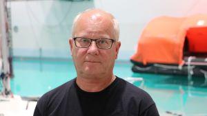En man i glasögon står framför en stor bassäng med en livbåt i bakgrunden.