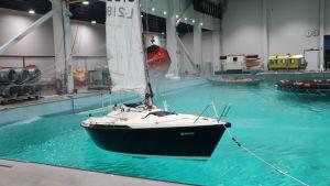 En segelbåt i en bassäng med en aktiv vågmaskin.