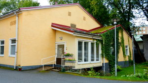 ett hus med gula väggar och fönster och blomrabbat och grön klätterväxt på ena väggen