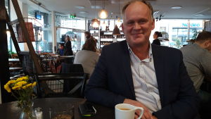 Owe Sjölund sitter på ett kafé med en kopp kaffe.