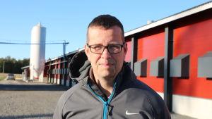 En man med kort mörkt hår och glasögon står framför en stor kalkonhall.