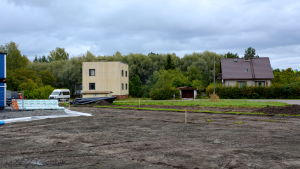 två hus, en uppgrävd åker och träd i bakgrunden