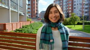en kvinna står i höstkläder på en bakgård med trästaket och höghus