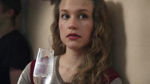 Skådisen Empuu (Julia Lappalainen ) kikar över kanten på sitt glas.