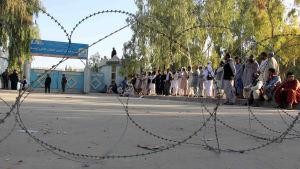 Väljare står och köar utanför en vallokal i Kandahar omgivna av taggtråd och beväpnade vakter.