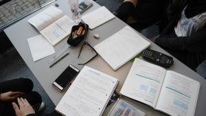 Ett bord fyllt med studietillbehör, häften, miniräknare och pennor.