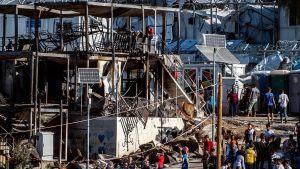 Flyktingar oich migranter som samlats vid containrar som brunnit ner i en brand i det överfyllda lägret Moria. En kvinna och ett barn omkom i branden 29.9.2019. Lesbos, Grekland 30.9.2019.