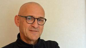 Porträtt på en man med svarta glasögon.
