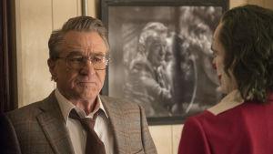 Närbild på Murray Franklin (Robert De Niro) som ser skeptisk ut då han ser på Joker.