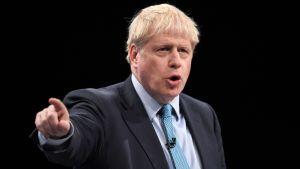 Boris Johnson i kostym, pekar sitt finger åt vänster.