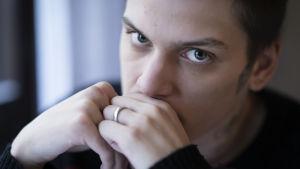 Miro Määttänen lähikuvassa ikkunan äärellä, pitää käsiään ajatuksissaan suun edessä.
