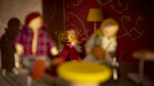 Pieni tyttönukke istuu yksin nukkekodin nurkassa. Edessä pöydän äärellä istuvat isä- ja äitinukke.