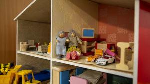 Pieni tyttönukke istuu nukkekodin toisessa kerroksessa harmaahiuksisen pariskunnan edessä lattialla. Ympärillä näkyy nukkekodin huonekaluja sekä pari pientä leluautoa.