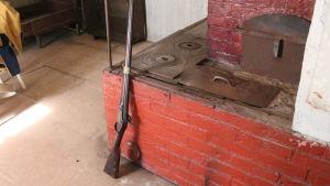 En gammal murad spis och ett muskötgevär som lutar mot den.