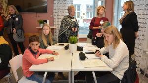 Elever vid ett bord i tklassrum, lärare står bakom och tittar på.