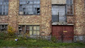 gammalt förfallet tegelhus, med röd dörr