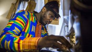 Dennis Owusu ompelemassa ompelukoneella