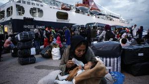 En kvinna matar sin baby efter att ha kommit i land från färjan Nissos Samos som tagit dem från ön Lesbos till hamnen i Pireus, Grekland  7.10.2019