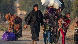 Kvinnor och barn flyr i norra Syrien. På bilden syns fyra barn och fyra kvinnor. En av kvinnorna bär ett större bylte på huvudet.