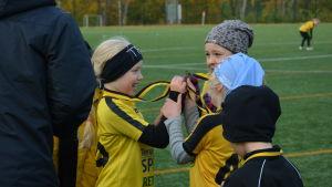 Sjuåriga fotbollsflickor firar med medaljer