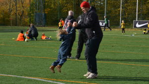 Pappa med barn på fotbollsplan