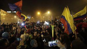 Folksamling i Ecuador. Bilden är tagen på kvällen och man ser ett hav av människor och en handfull av landets flaggor, mobiltelefoner och vad som ser  ut att vara en vuvuzela.